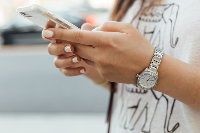 close up of woman holding and using a smartphone